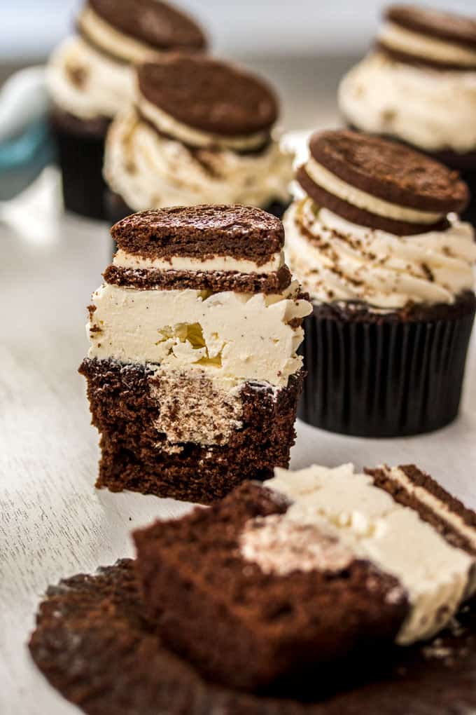 A chocolate cupcake with white frosting and a cookie sitting on top that has been cut in half. It is surrounded by more cupcakes.