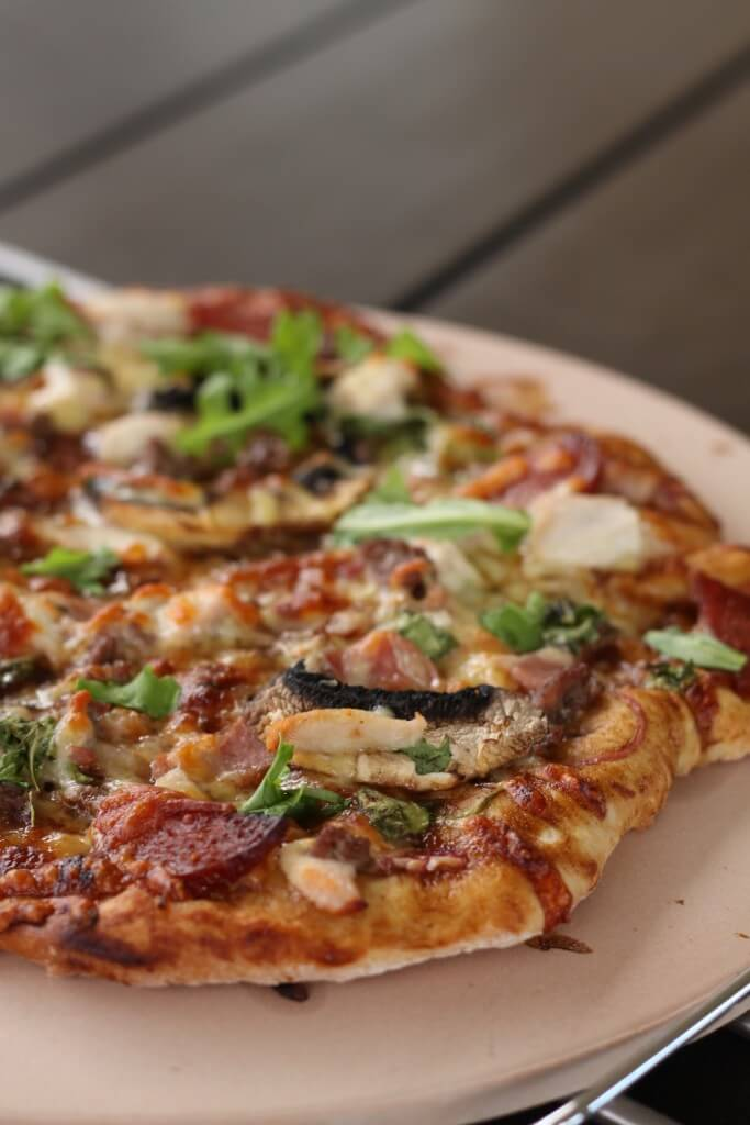 Close up of a pizza with meat and mushroom topping on a ceramic pizza tile
