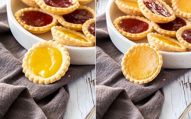 Lemon Curd and Orange Curd filled jam tarts leaning up against a white platter filled with jam tarts. It sits on top of a dark grey tea towel