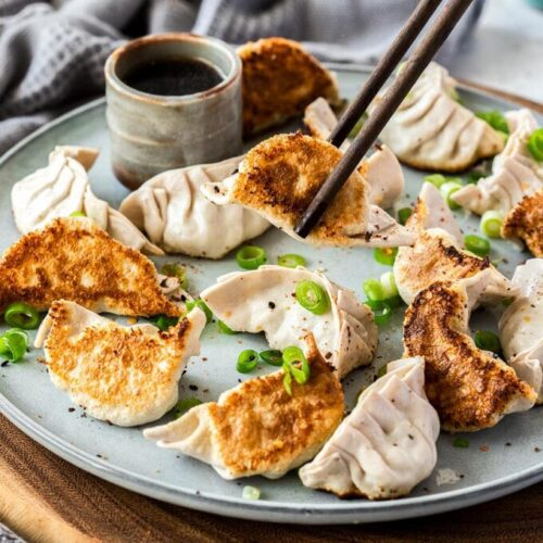 Chopsticks picking up a pork gyoza from a plate of 16. The grey plate sits on a wooden platter. A small grey pot of dipping sauce behind them.