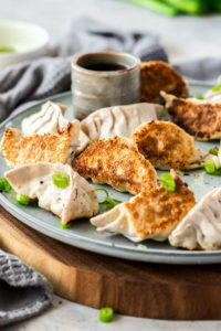 10 pork gyoza on a grey plate on a wooden platter. A small grey pot of dipping sauce behind them.