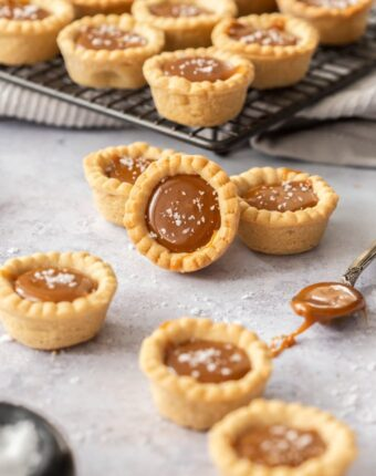 A group of caramel cookie cups on a grey surface. A spoon filled with caramel next to them and a rack of more cookies behind