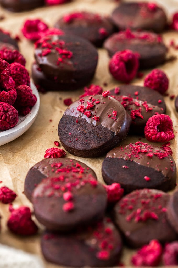 A batch of dark chocolate shortbread cookies, sprinkled with freeze-dried raspberries on a sheet of brown baking paper