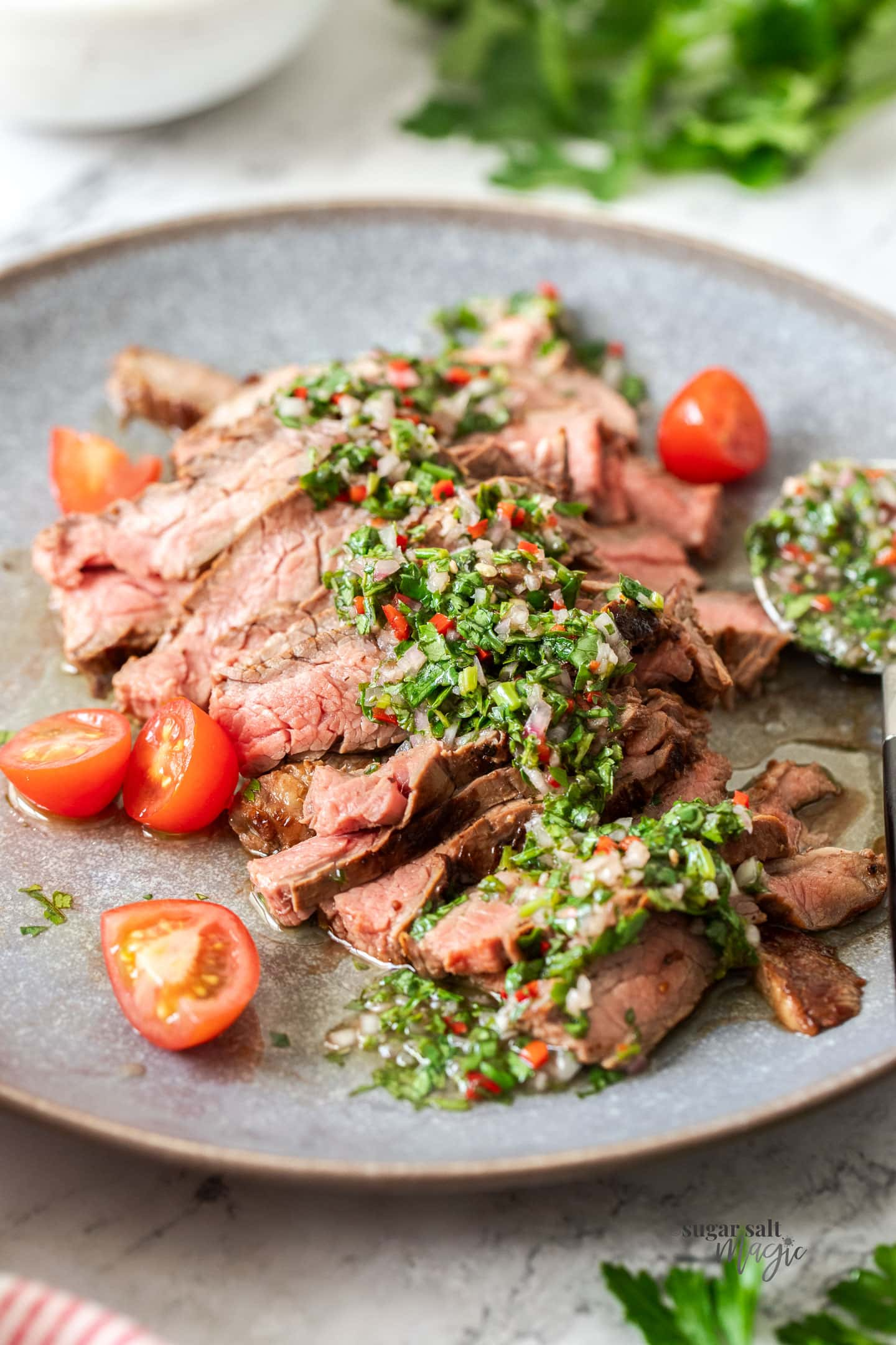 Sliced steak on a grey plate with green sauce over it.