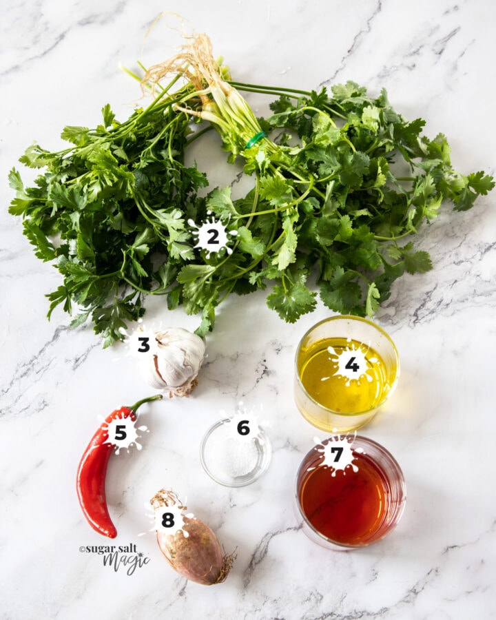 Ingredients for chimichurri sauce on a marble background.