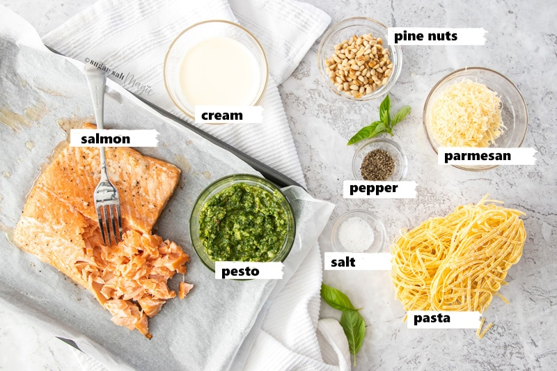 Ingredients for salmon pesto pasta laid out on a grey background