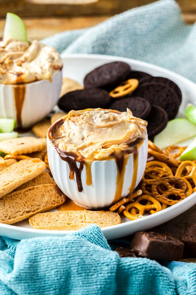 A small white bowl fillled with Snickers Cheesecake Dip surrounded by cookies, pretzels and slices of apple
