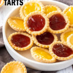 A white platter filled with jam tarts on a dark grey tea towel