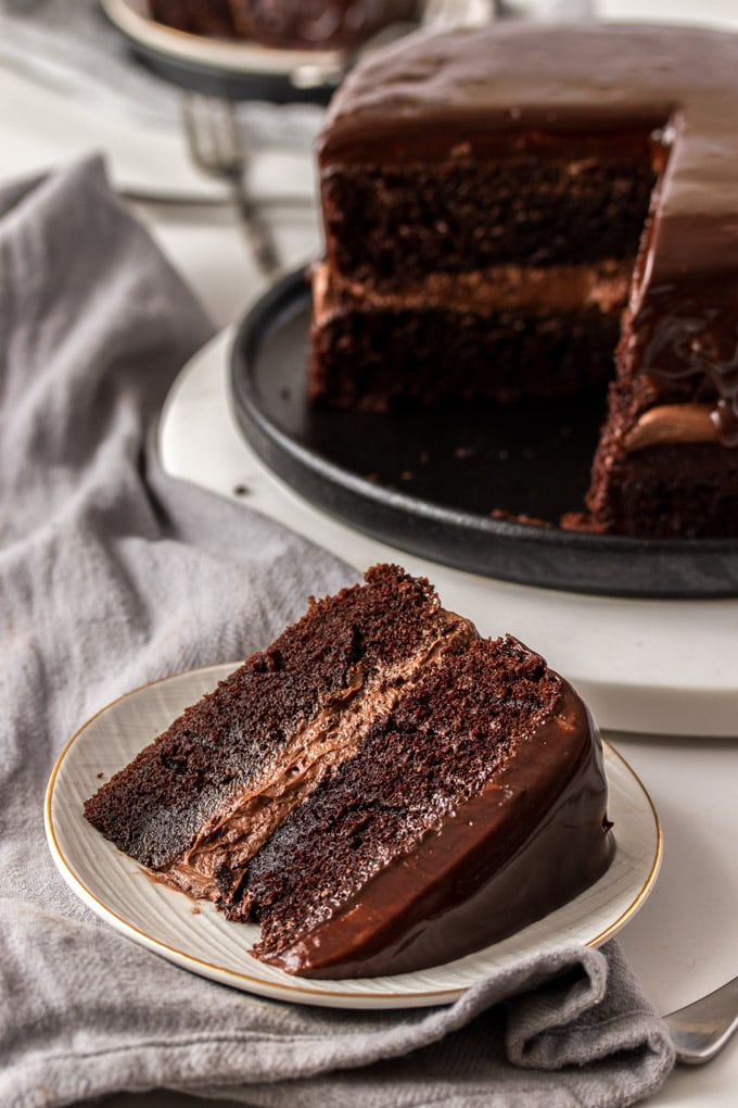 A slice of chocolate cake on a plate, with the rest of the cake in the background