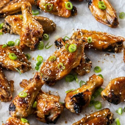 A group of sticky asian chicken wings on a sheet of baking paper with spring onions sprinkled over them
