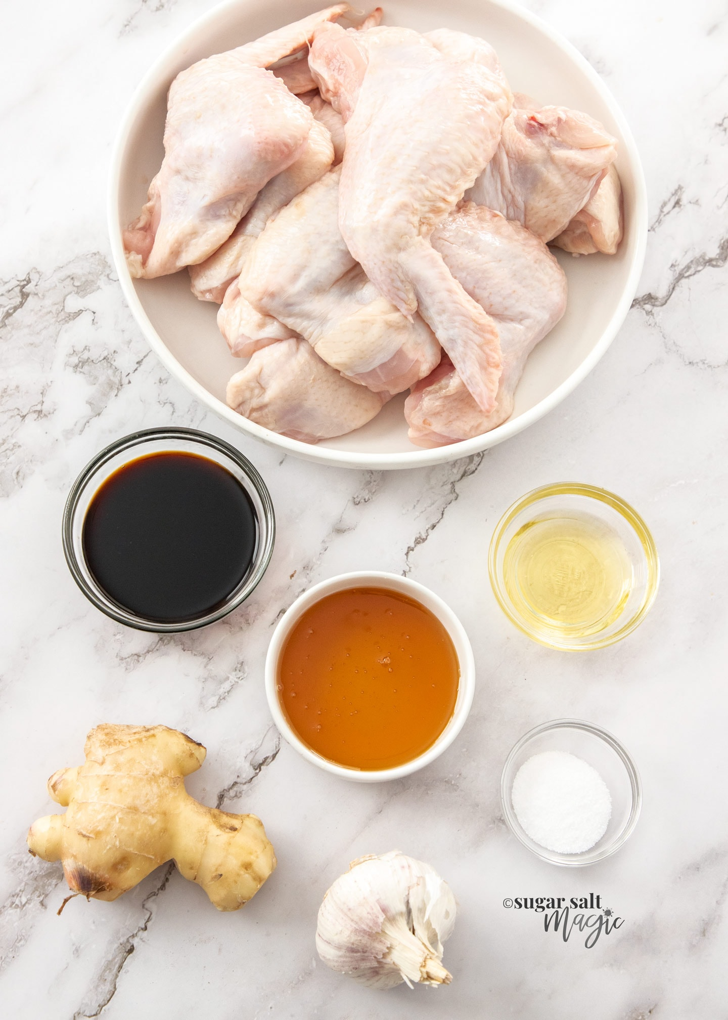 Ingredients for sticky chicken wings on a marble bench top.