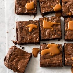 9 brownies on a white baking paper with caramel drizzle over them