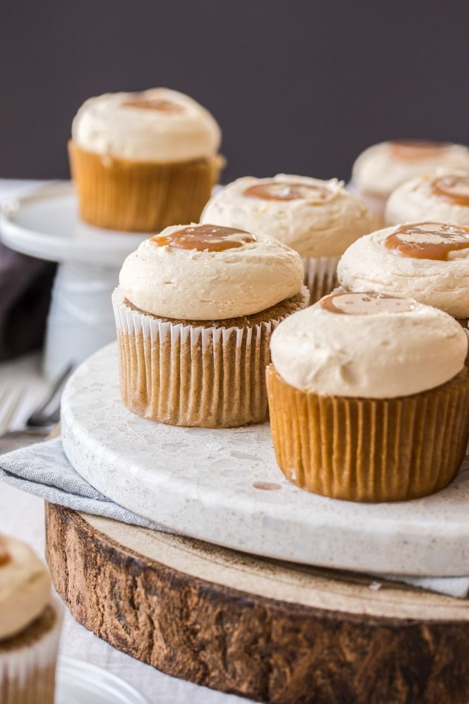 Cinnamon Cupcakes sitting on a marble platter and wooden platter