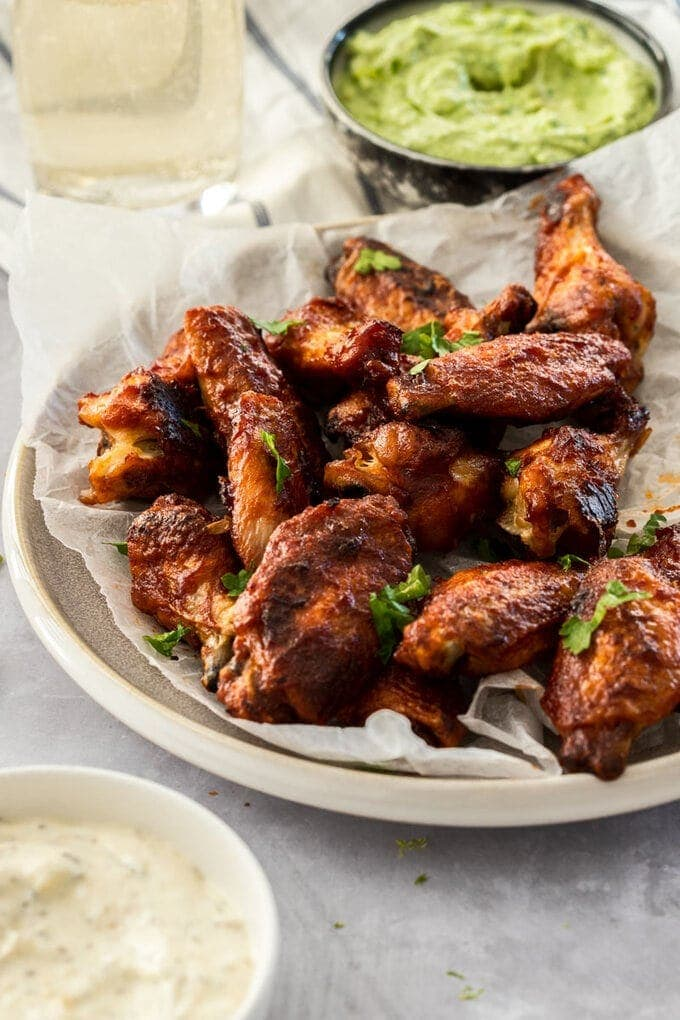 BBQ chicken wings on baking paper on a grey plate. A bowl of ranch dip sits in front and avocado dip sits behind.