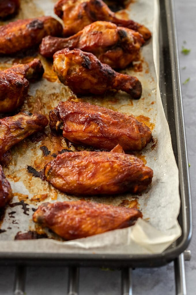 Chicken wings on a baking paper lined baking tray.