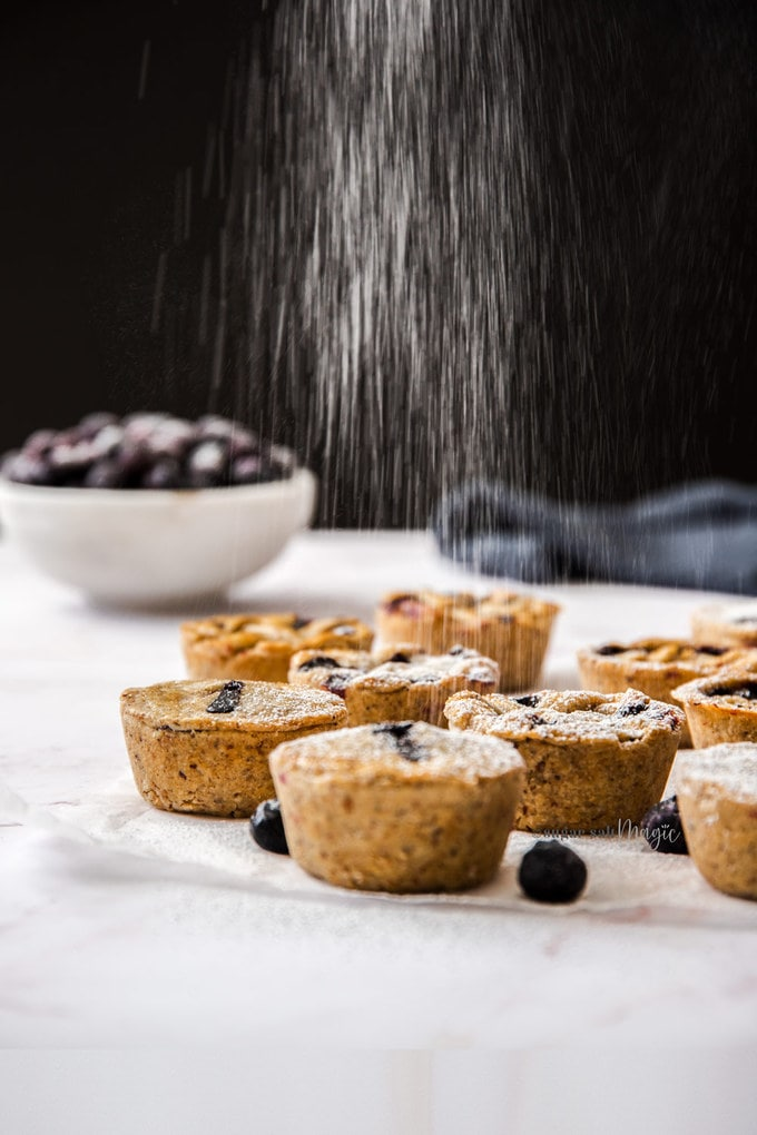 Icing sugar raining down onto some mini blueberry pies. A bowl of blueberries sits in the background