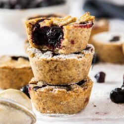 A stack of 3 mini blueberry pies with more surrounding it. A white bowl full of blueberries sits in the background