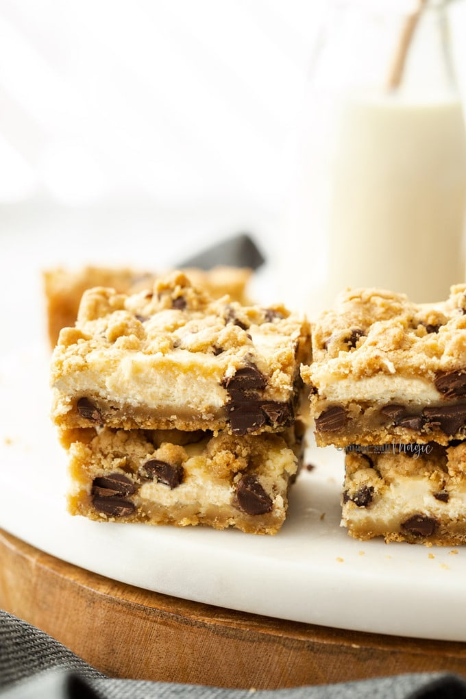 A stack of chocolate chip cheesecake bars on a marble platter with a jug of milk in the background