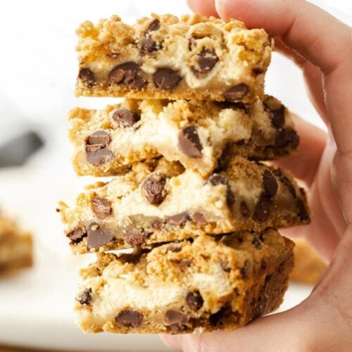A hand holding 4 chocolate chip cheesecake bars