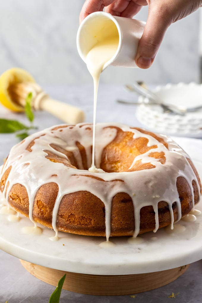 A vanilla bundt cake on a marble cake plate being drizzled with lemon icing from a small white jug
