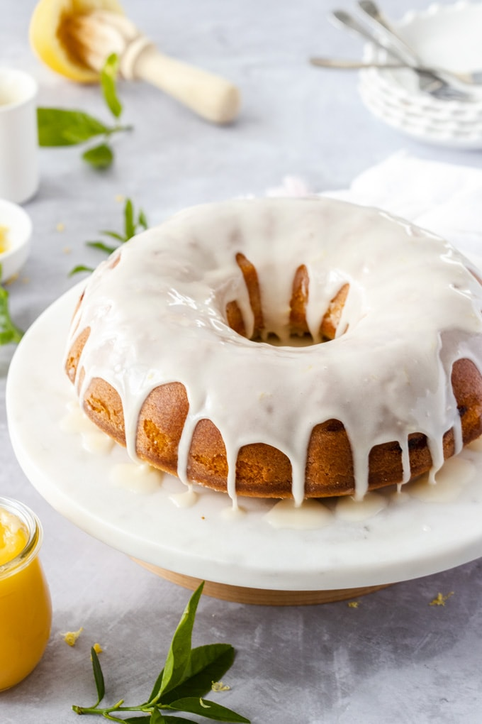 A bundt cake covered in white icing on a cake stand