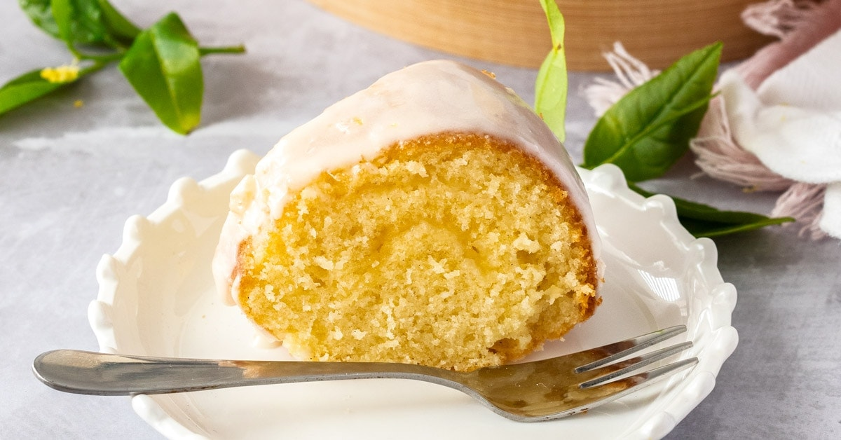 A slice of vanilla butter cake on a white cake plate with a fork in front. Some lemon tree leaves sit around it