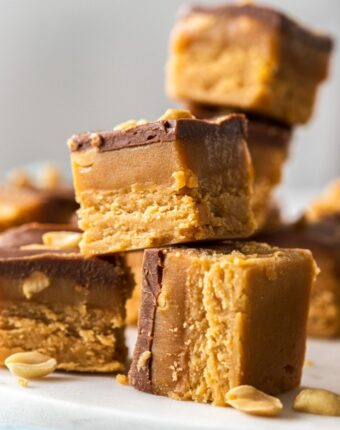 Pieces of caramel peanut fudge stacked up on a white platter