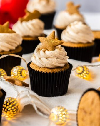A group of gingerbread cupcakes on a white table cloth, surrounded by christmas bauble lights