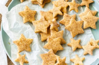 Birdseye view of a pastel green plate topped with star-shaped shortbread cookies