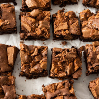 Top down view of a batch of 16 brownies on a sheet of white baking paper