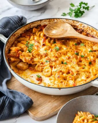 A white pan filled with creamy red pasta bake. A grey tea towel sits next to it. A wooden spoon on top.