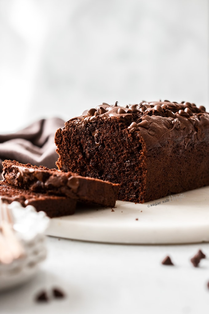 A chocolate loaf cake with slices cut from it