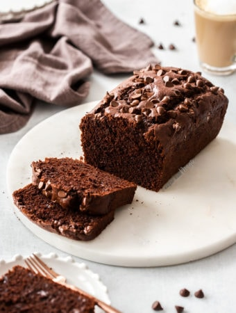 Chocolate loaf cake on a marble platter, with some slices cut from it