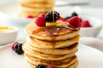 A stack of pancakes on a white plate with berries and maple syrup being poured over them.