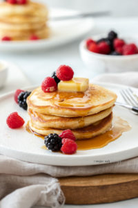 A stack of 3 pancakes on a white plate, topped with berries and butter