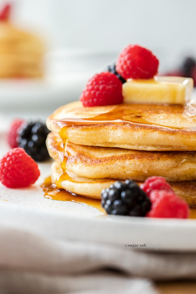 Close up of a stack of 3 pancakes on a white plate, topped with berries and butter