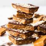 A stack of almond roca buttercrunch toffe,e covered in chocolate and almonds