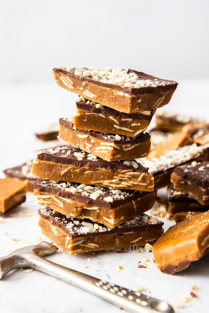 A stack of 7 almond roca buttercrunch toffee surrounded by other pieces of almond roca