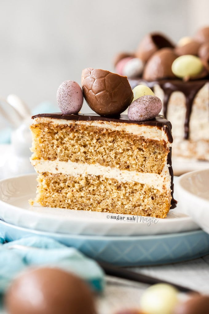 A slice of hazelnut cake topped with easter eggs on a white plate