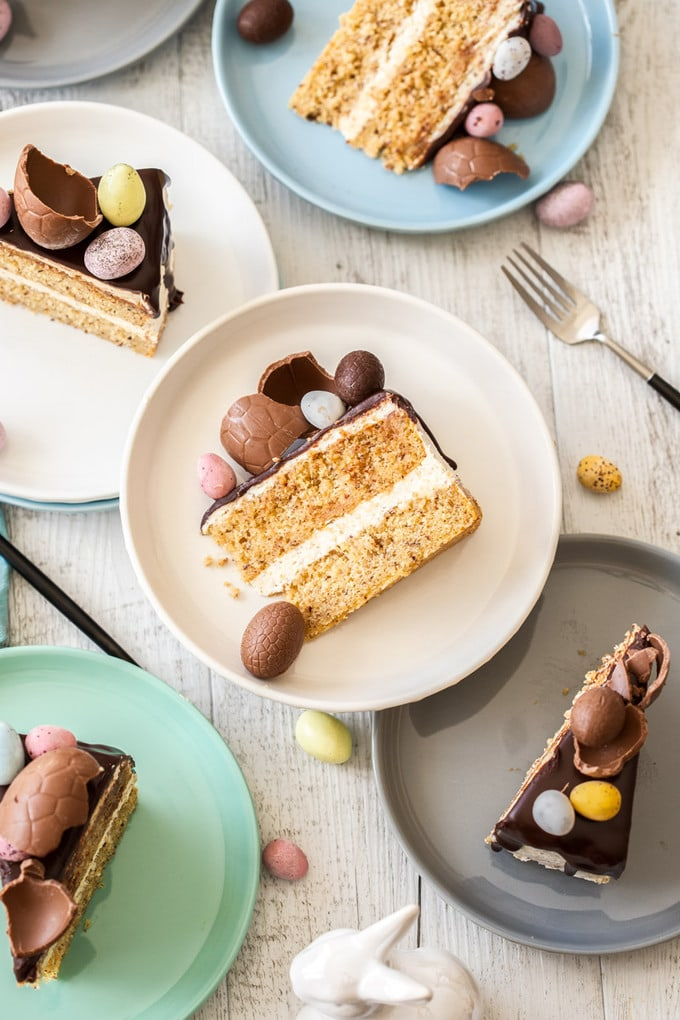 Slices of cake on different coloured plates surrounded by easter eggs