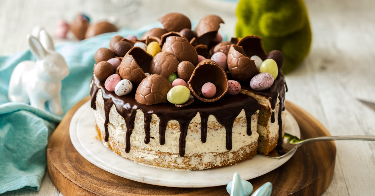 A cake topped with easter eggs and chocolate ganache on a marble plate, then on a wooden surface.