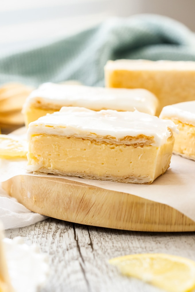 A closeup of a piece of vanilla custard slice with more in the background. It sits on a wooden board