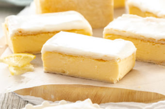 A batch of vanilla custard slice on a sheet of baking paper on a wooden board. Once sits on a plate in front with a bite taken out