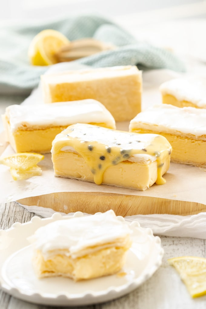 A batch of vanilla custard slice on a sheet of baking paper on a wooden board. One is topped with passionfruit icing