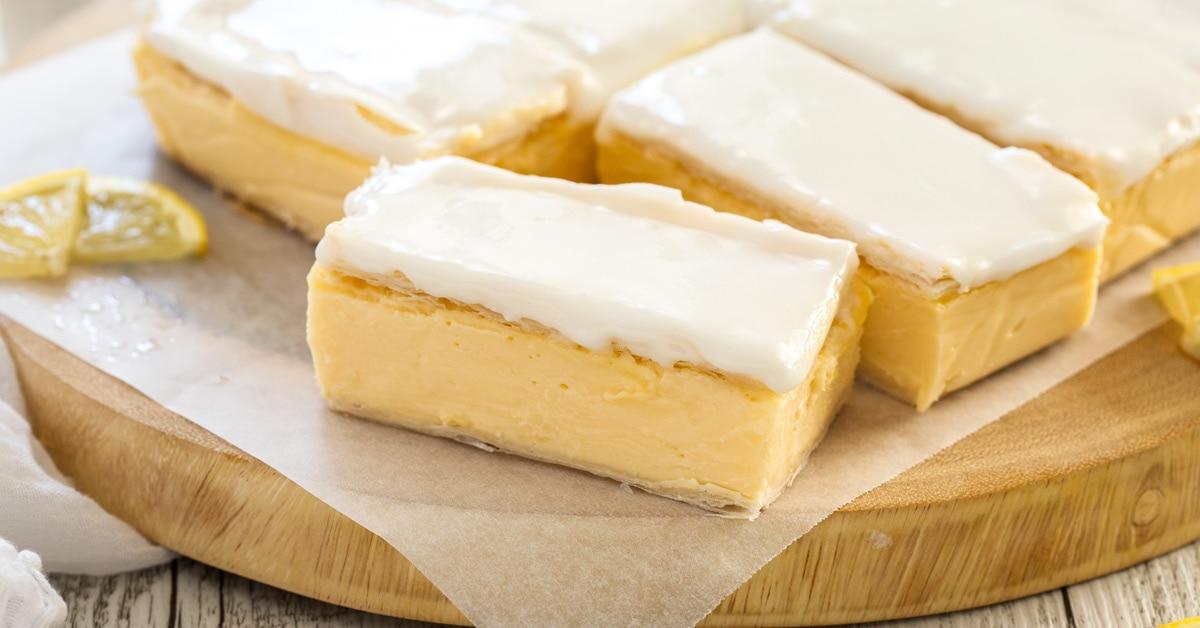 A batch of vanilla custard slice on a sheet of baking paper on a wooden board.
