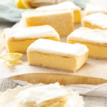 A batch of vanilla custard slice on a sheet of baking paper on a wooden board. One sits on a plate in front with a bite taken out