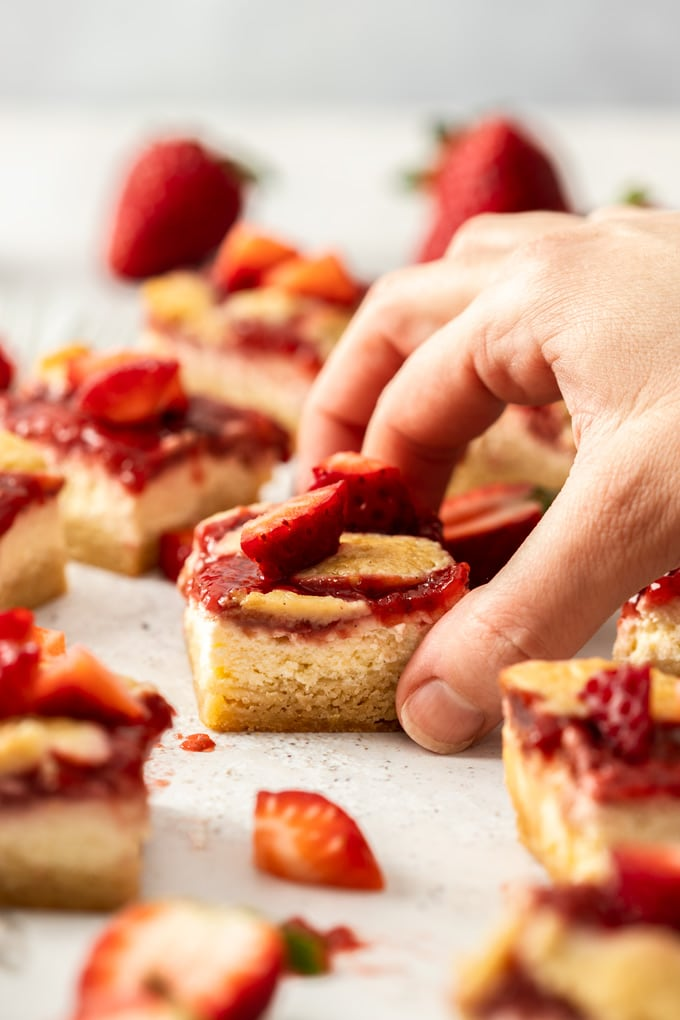 A hand reaching in to pick up a strawberry cheesecake bar off a grey tile