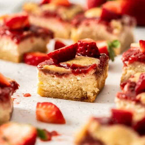 A cheesecake bar topped with strawberry topping sitting on a white background surrounded by strawberries and more bars