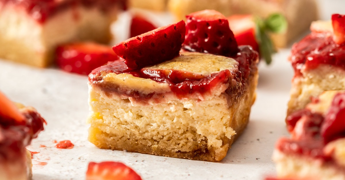 Extreme closeup of a strawberry cheesecake bar showing the 3 layers - blondie, cheesecake, strawberry topping