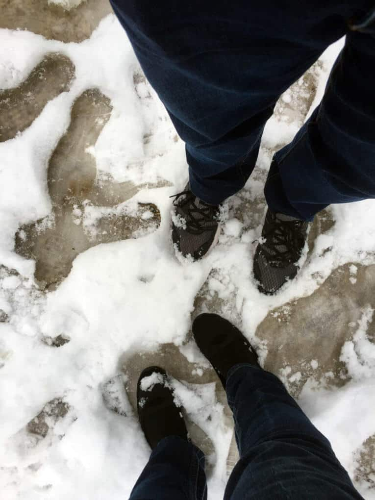 Footprints and feet in the snow.